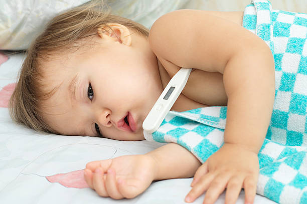 Baby ailing and lying with thermometer stock photo