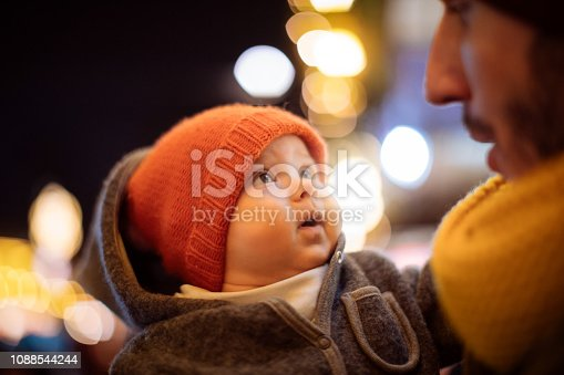 Baby looking at her father in Christmas time.