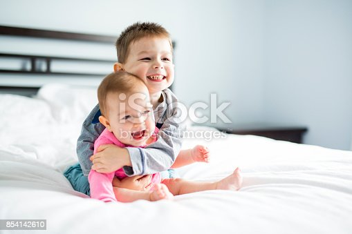istock baby and his brother on bed 854142610