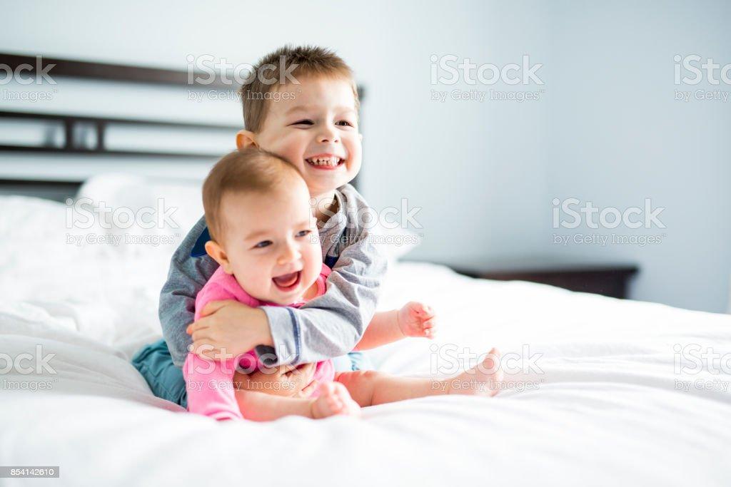 bébé et son frère sur le lit - Photo