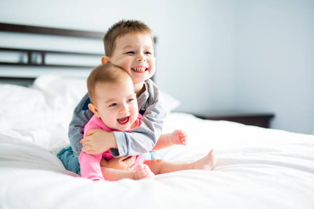 baby and his brother on bed - sister stock photos and pictures