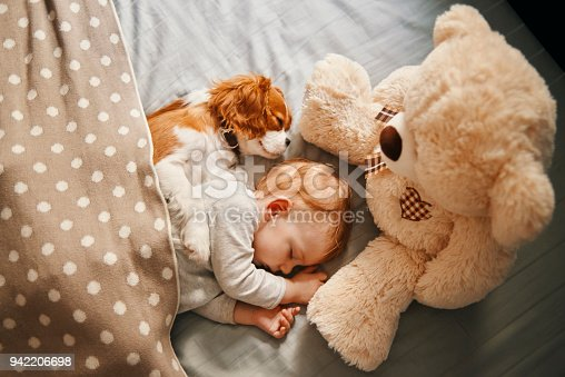 942206906 istock photo baby and his puppy sleeping peacefully 942206698