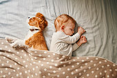 istock baby and his puppy sleeping peacefully 942206862
