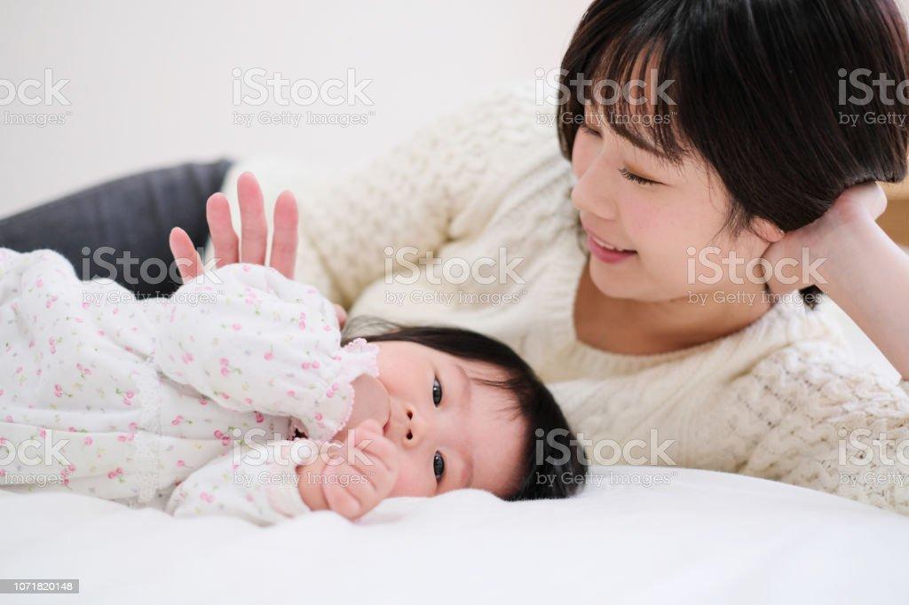 赤ちゃんと母親のベッドに横になっています。 ストックフォト