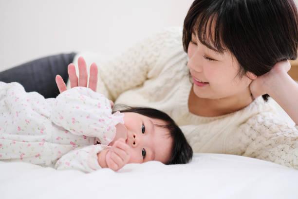 赤ちゃんと母親のベッドに横になっています。 - 母親 ストックフォトと画像