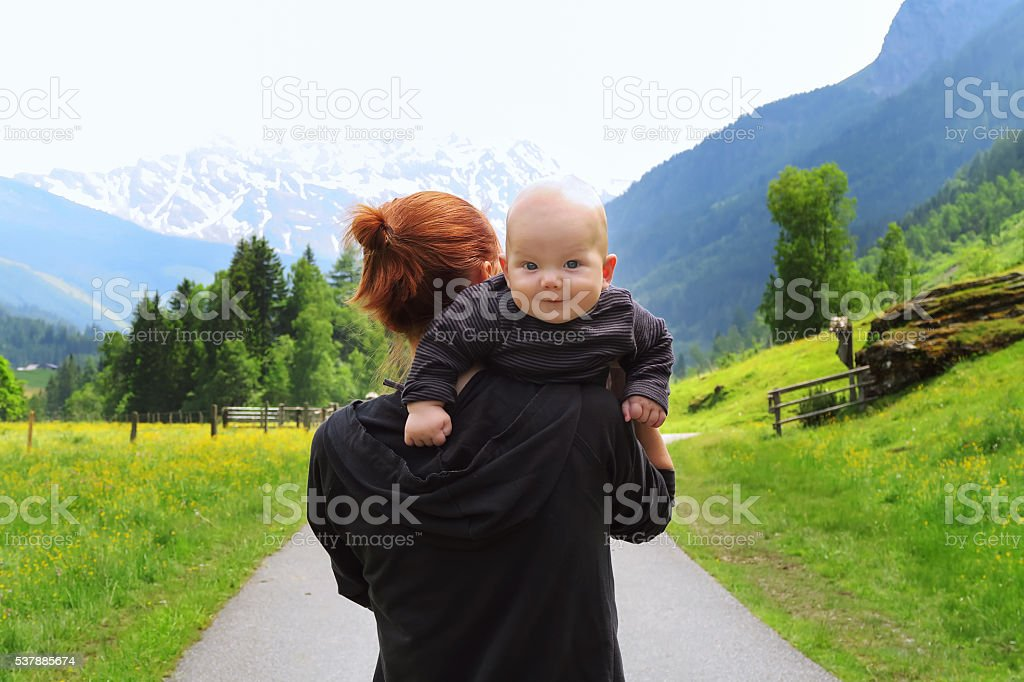 Baby and mother on the Alps mountains in the Background stock photo