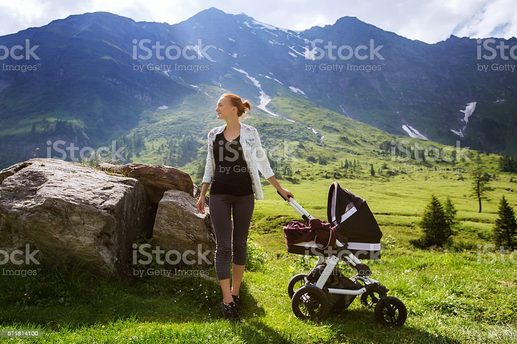Baby and mother with the Alps mountains in nature stock photo