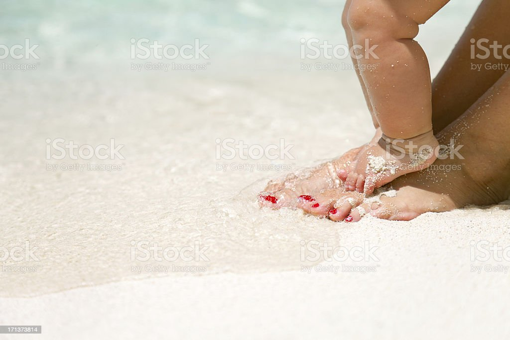 baby and mother's feet at a tropical Caribbean beach stock photo