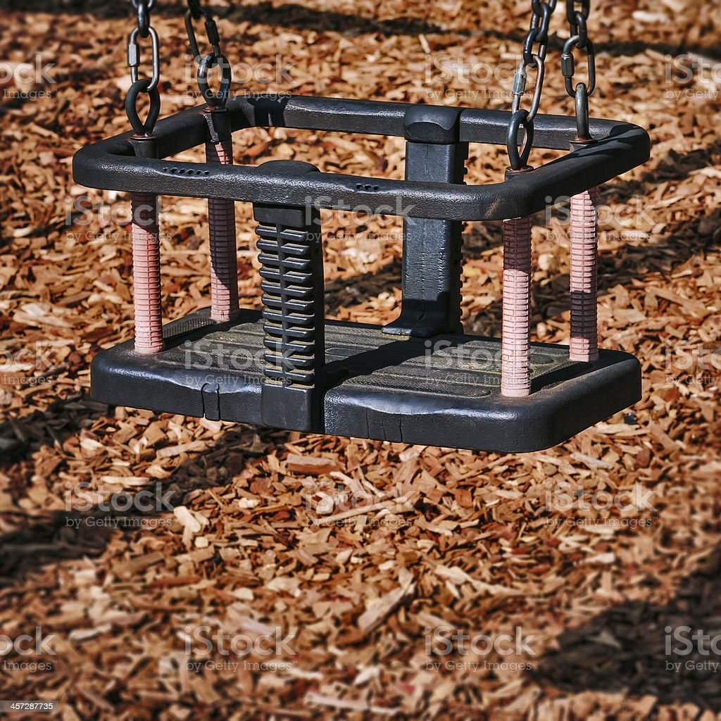 Baby and toddler swing empty in the playground square composition royalty-free stock photo