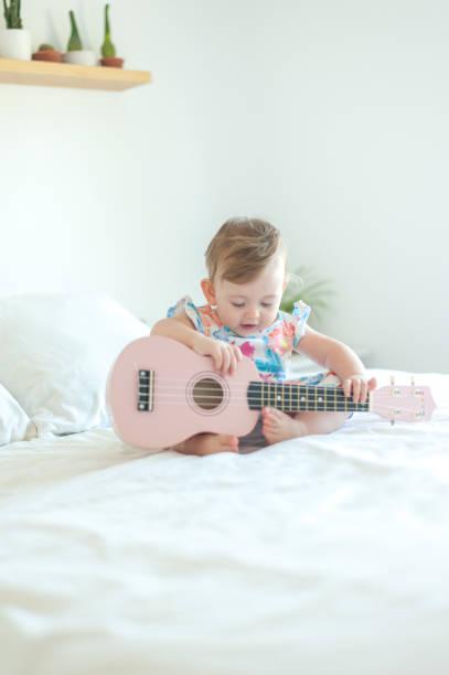 Baby and  ukulele stock photo