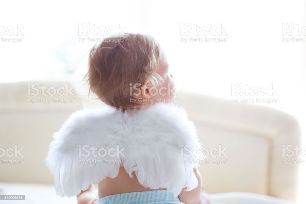 Baby angel Baby girl is sitting on bed, wearing small fluffy angel wings. Rear view. 6-11 Months Stock Photo
