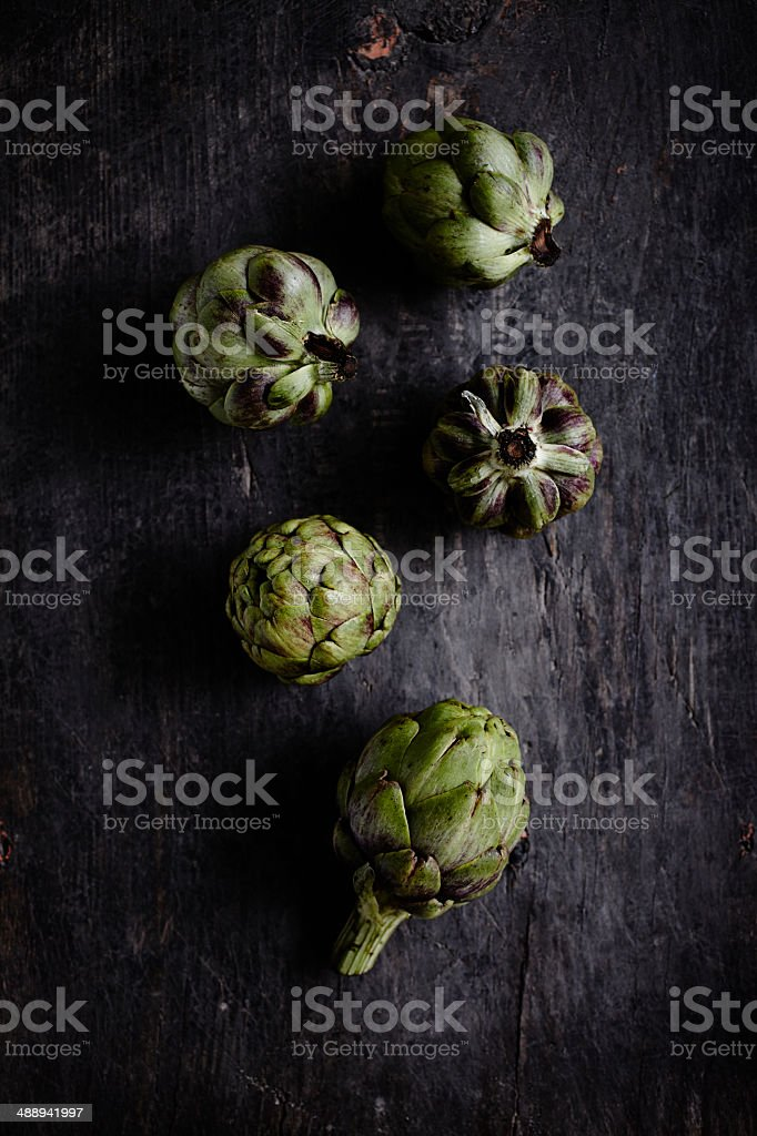 Baby artichokes on dark rustic wooden table. stock photo