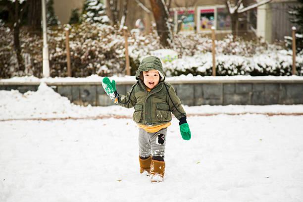 baby auf spielplatz im schnee - kinder winterstiefel stock-fotos und bilder