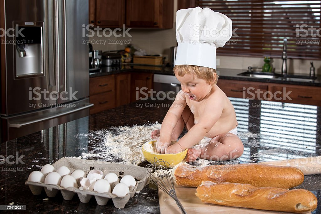 Baby Baker Sitting in Kitchen stock photo