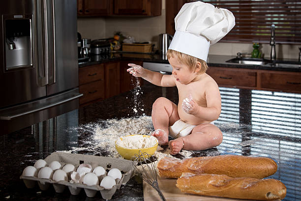 Baby Baker Sitting in Kitchen stock photo