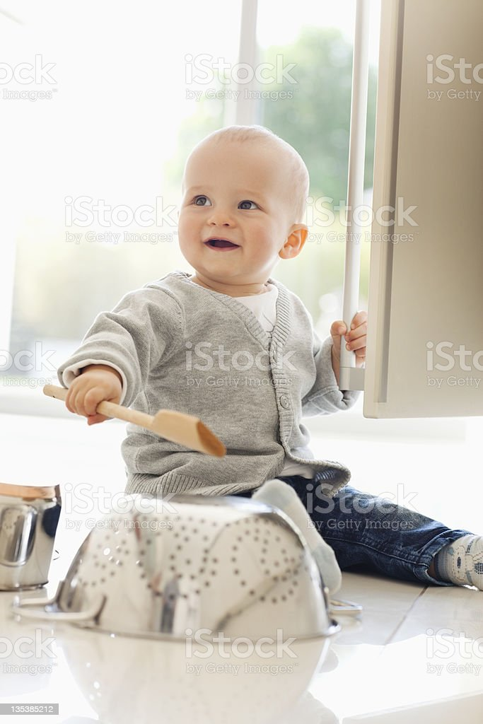 Baby banging on colander with wooden spoon royalty-free stock photo