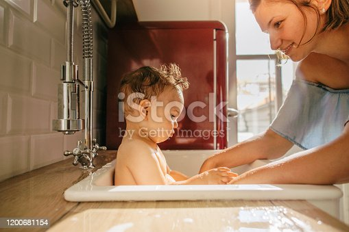 Photo of a baby having a bath in a kitchen sink