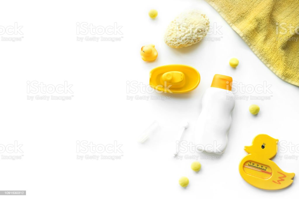 Baby bath products flat lay. Children cosmetics set: rubber duck, towel, shampoo, soap, scissors, sponge, hair and tooth brush isolated on white. Copy space for text stock photo
