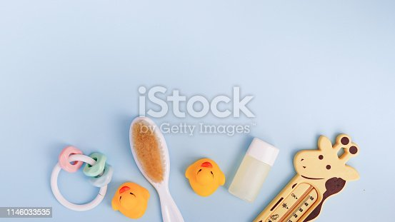 istock Baby bath products on blue background with copy space. flat lay soap bar, yellow rubber duck and liquid soap, toy 1146033535