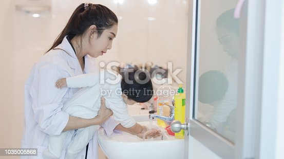 1134841078 istock photo baby bathing with her mother in the bath room. 1035005868