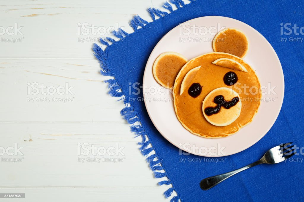 Baby bear on a pink plate stock photo