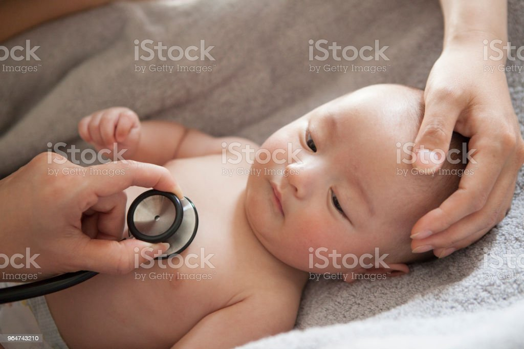 A baby being heard heart sounds in a stethoscope. royalty-free stock photo