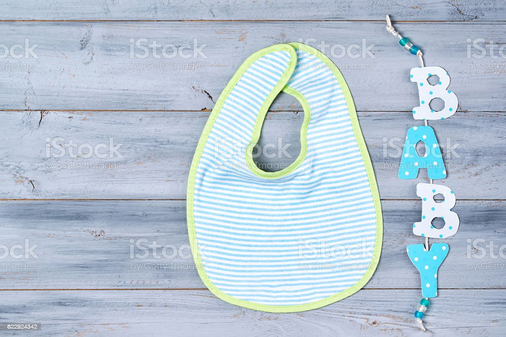 Baby bib and word baby on wooden background stock photo