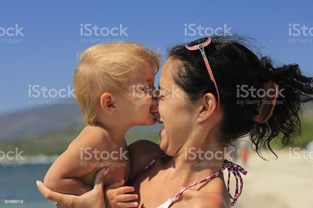 baby biting her mother's nose stock photo
