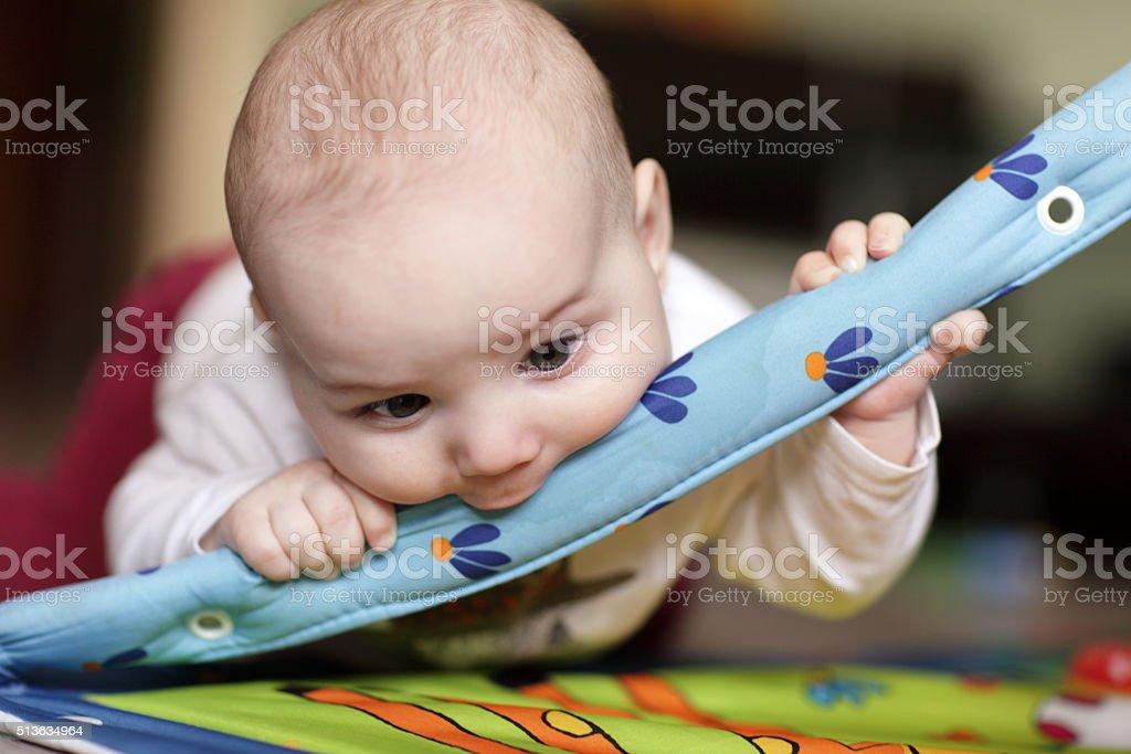 Baby biting playing mat stock photo