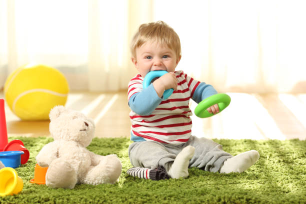 Baby biting toys on a carpet stock photo
