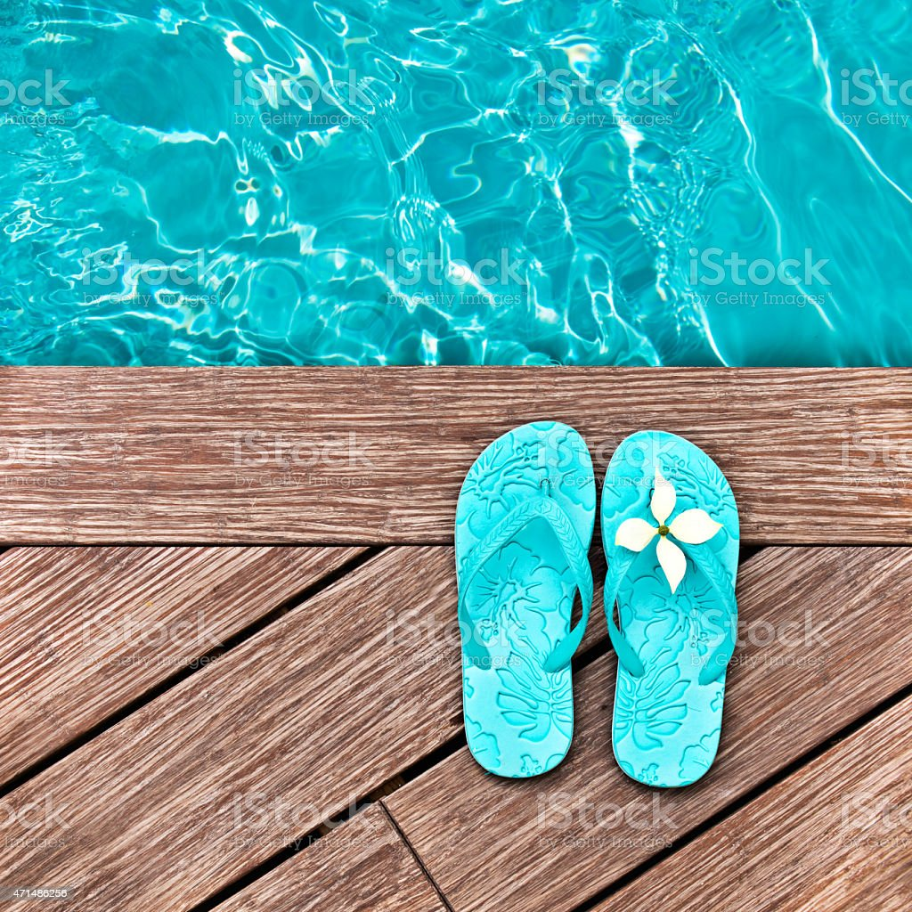 Baby blue flip flops on a deck next to the pool stock photo