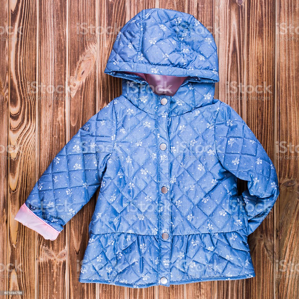 Baby blue warm jacket on wooden background foto stock royalty-free