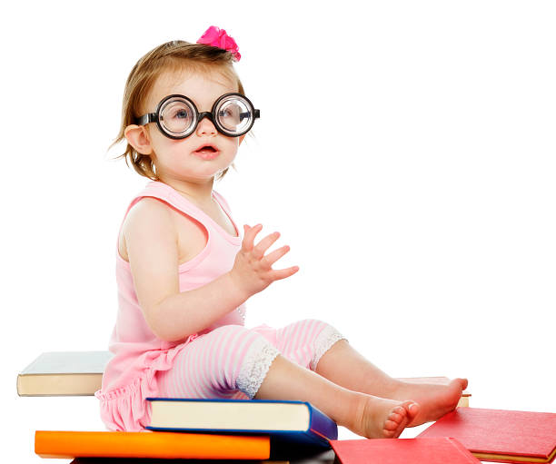 Baby bookworm: little girl in horn-rimmed spectacles with books stock photo