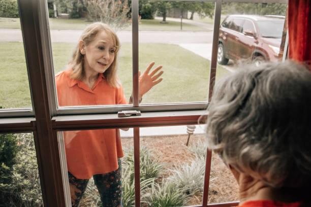 een baby boomer dochter een bezoek aan haar bejaarde shut-in moeder in haar jaren '80 tijdens quarantaine van covid-19 coronavirus door een raam om niet te vangen deze besmettelijke ziekte - raam bezoek stockfoto's en -beelden