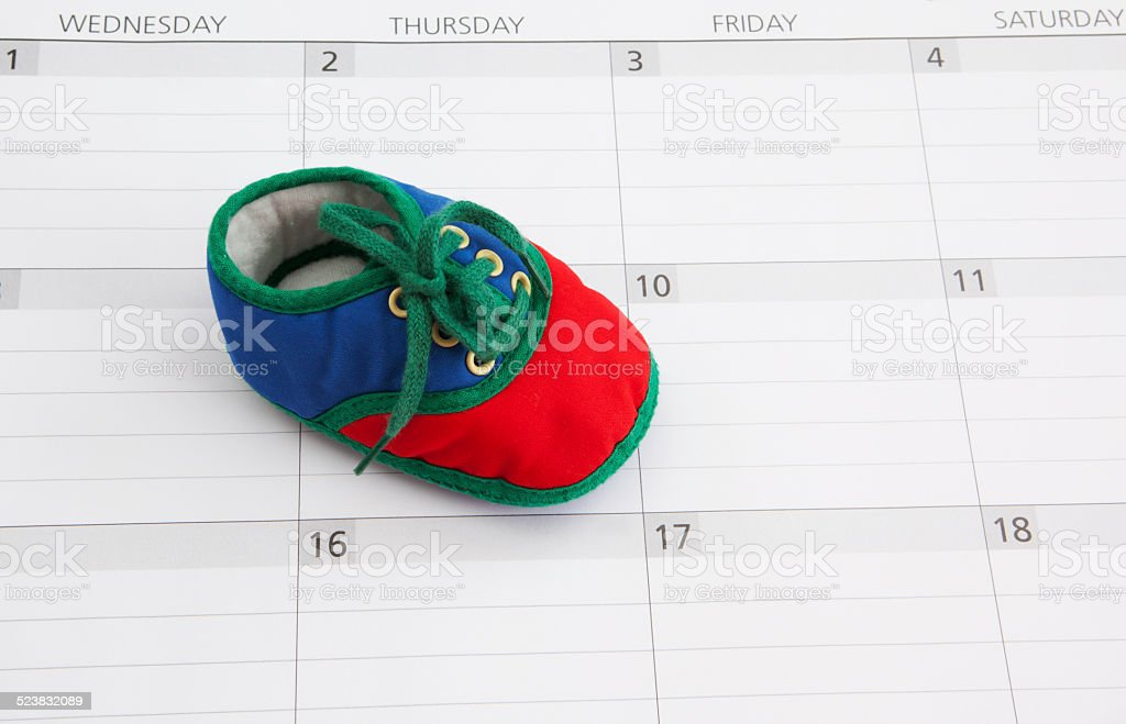 Baby Bootie on Calendar Background stock photo
