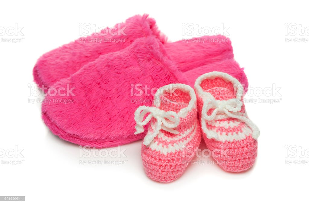 Baby booties and  mom's  slippers stock photo