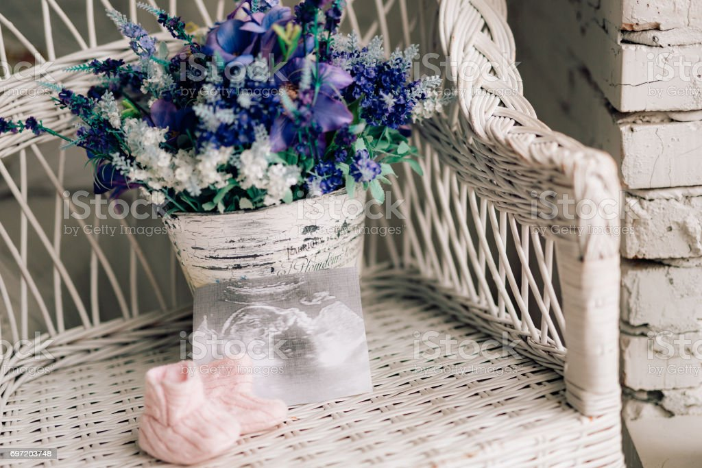 Bottillons bébé sur une chaise en osier et un bouquet de lavande sur un ba - Photo