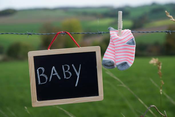 baby born ankündigung, kleine gestreifte socken und kreide vorstand stacheldraht hängen - horizontal gestreiften vorhängen stock-fotos und bilder