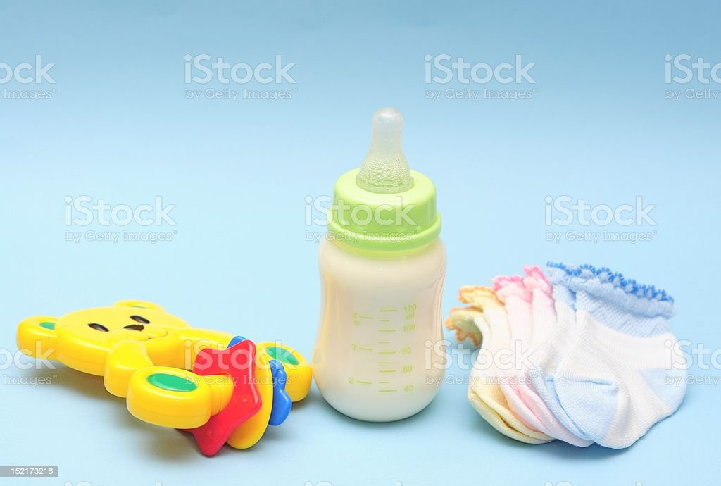 Baby bottle, rattle and sock stock photo