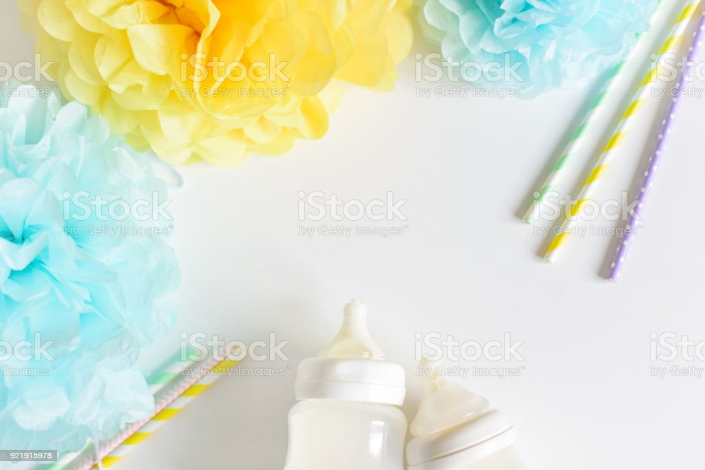 Baby bottle with breast milk, various festive paper decor. It's a boy or baby birthday celebration concept. Baby shower concept. Top view, free copy space. stock photo
