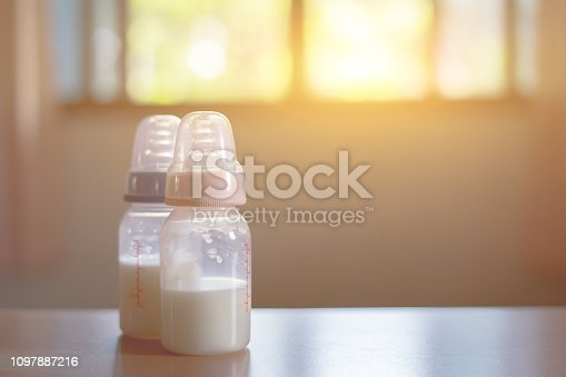 istock Baby bottle with milk and a measuring scale on the background of a lot of full bottles of breast milks, the most healthy food for newborn,vintage color 1097887216
