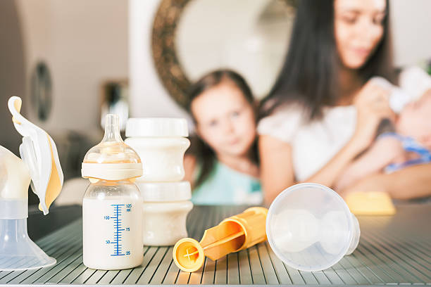 Baby bottle with milk and manual breast pump - foto de acervo