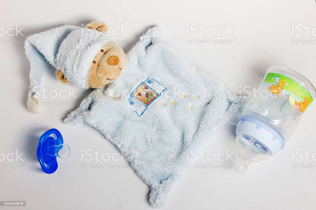 Baby bottles, pacifiers and toys lying on a white background. foto