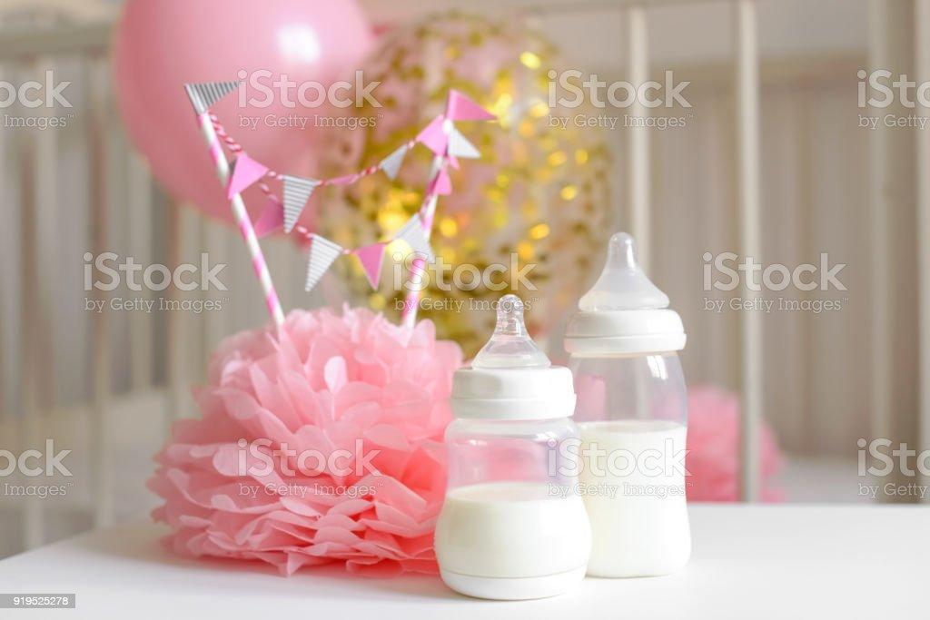 Baby bottles with breast milk with various festive paper decor and balloons in front of baby bedroom. It's a girl or baby birthday celebration concept. Baby shower concept. stock photo
