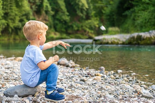 child alone with blond hair, throws a stone on the bank of the river,sunny day,horizontal photo