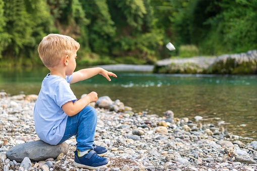 baby boy alone throwing a stone on river