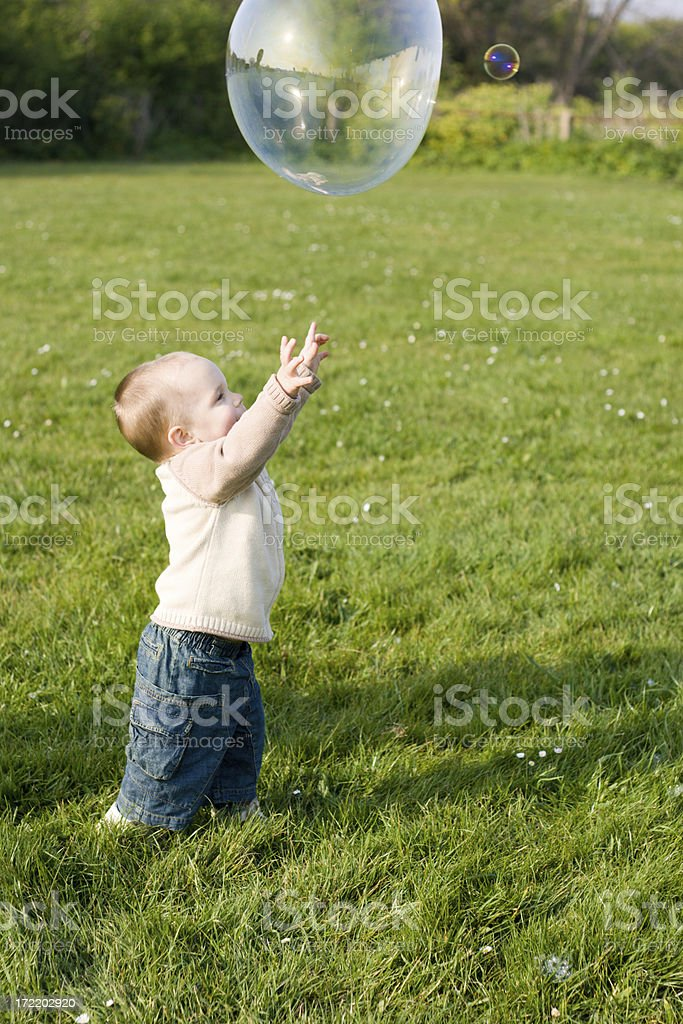 Baby boy and giant soap bubble royalty-free stock photo
