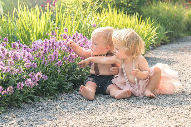 Baby boy and girl in a garden stock photo