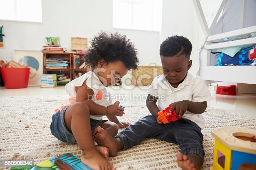 istock Baby Boy And Girl Playing With Toys In Playroom Together 860908340