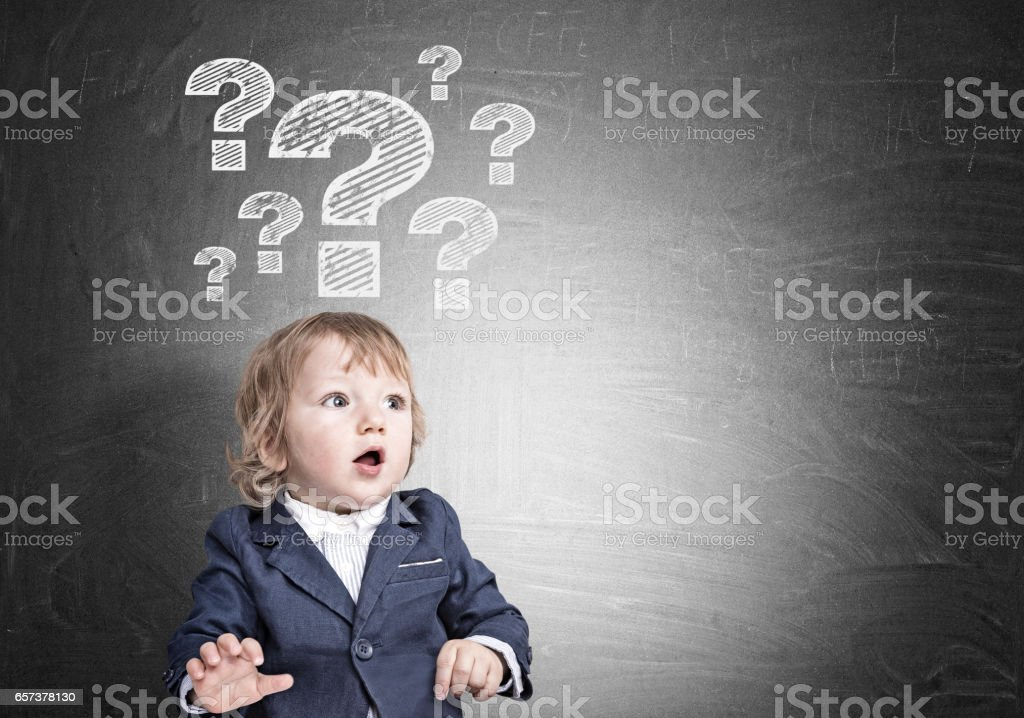 Baby boy and question marks on blackboard stock photo